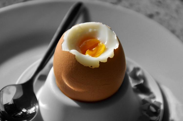 uovo cucinato alla coque su porta uovo e cucchiaino